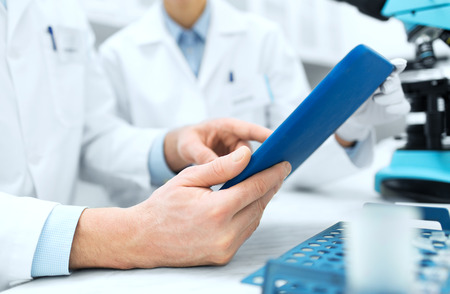 clinical: science, chemistry, technology, biology and people concept - close up of scientists hands with tablet pc in lab Stock Photo