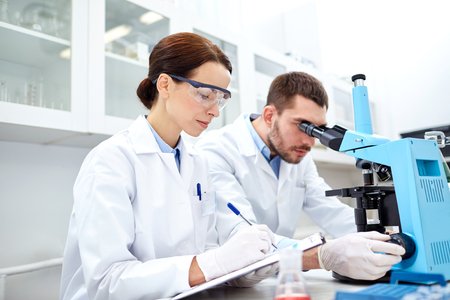 química: ciencia, química, tecnología, biología y concepto de las personas - jóvenes científicos que sacuden el vidrio con el reactivo y haciendo prueba o investigación en laboratorio clínico