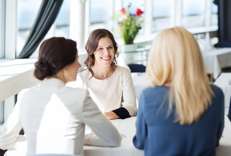 mid age: people, communication and lifestyle concept - happy women meeting and talking at restaurant