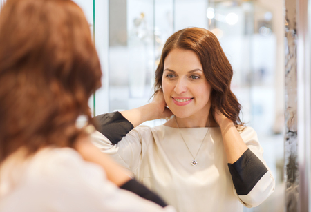 consumerism: sale, consumerism, shopping and people concept - happy woman choosing and trying on pendant at jewelry store Stock Photo