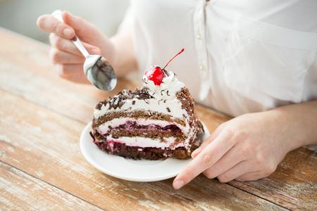 Lebensmittel, Junk-Food, kulinarisch, backen und Ferien-Konzept - Nahaufnahme von Frau essen Schokolade-Kirsch-Torte mit Löffel und sitzen am Holztisch