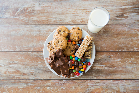 oatmeal cookie: junk food, sweets and unhealthy eating concept - close up of candies, chocolate, muesli and cookies with milk glass on plate
