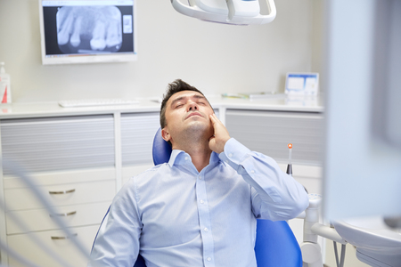 stomatology: people, medicine, stomatology and health care concept - unhappy male patient having toothache sitting on dental chair at clinic office Stock Photo