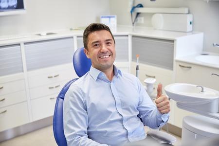 mensen, geneeskunde, stomatologie en gezondheidszorgconcept - gelukkige mannelijke geduldige zitting op tandstoel en het tonen van duimen omhoog op kliniekkantoor