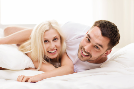 men and women: people, family, bedtime and happiness concept - happy couple lying in bed at home Stock Photo