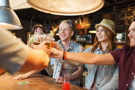 bar: people, leisure, celebration and party concept - group of happy smiling friends clinking glasses with drinks at bar or pub