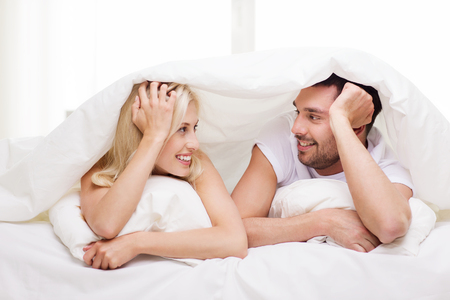 people, family, bedtime and happiness concept - happy couple lying in bed covered with blanket over head and talking at home Фото со стока