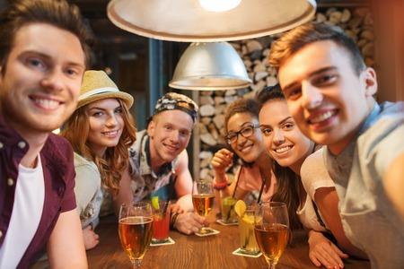 jovenes tomando alcohol: la gente, el ocio, la amistad, la tecnología y el partido concepto - grupo de amigos felices sonriendo con teléfono inteligente y bebidas que toman autofoto en el bar o pub Foto de archivo