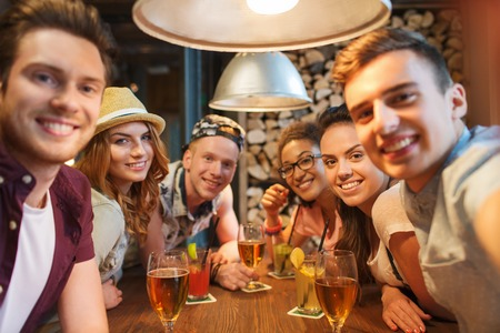 drinking alcohol: people, leisure, friendship, technology and party concept - group of happy smiling friends with smartphone and drinks taking selfie at bar or pub