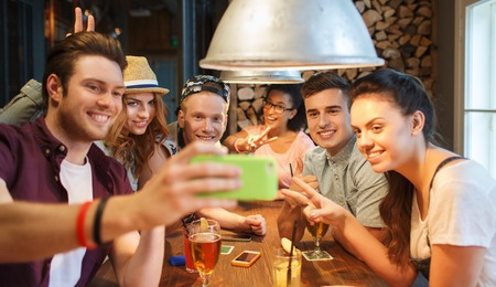 customer: people, leisure, friendship, technology and communication concept - group of happy smiling friends with smartphone and drinks taking selfie at bar or pub