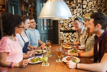 la gente, il tempo libero, l'amicizia e il concetto di comunicazione - gruppo di amici sorridenti felici di mangiare, bere e parlare al bar o pub