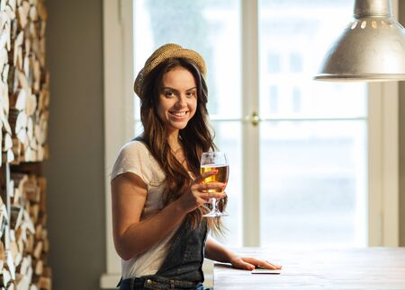 non alcoholic beer: people, drinks, alcohol and leisure concept - happy young redhead woman drinking beer at bar or pub Stock Photo