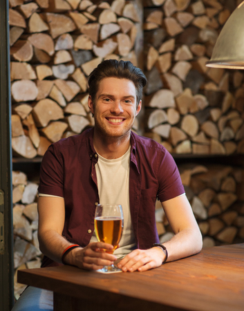 non alcoholic beer: people, drinks, alcohol and leisure concept - happy young man drinking beer at bar or pub Stock Photo