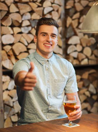 non alcoholic beer: people, drinks, alcohol, gesture and leisure concept - happy young man drinking beer and showing thumbs up at bar or pub Stock Photo