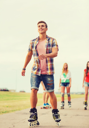 rollerblade: holidays, vacation, love and friendship concept - group of smiling teenagers with roller skates and skateboard riding outdoors