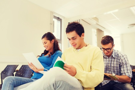 taking notes: education, high school, teamwork and people concept - group of smiling students with notepads sitting in lecture hall Stock Photo