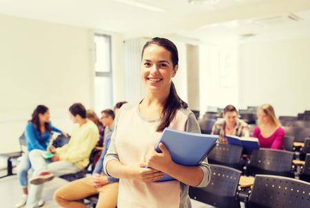 onderwijs: onderwijs, middelbare school, teamwork en mensen concept - groep lachende studenten met notitieblokken zitten in collegezaal