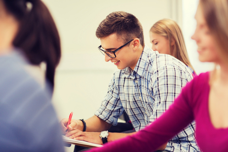 school exam: education, high school, teamwork and people concept - group of smiling students with notebook sitting in lecture hall and writing Stock Photo