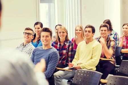 onderwijs, middelbare school, teamwork en mensen concept - groep lachende studenten met notebooks en leraar in de klas