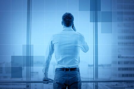 out of office: business, technology and people concept - businessman calling on smartphone and looking out office window behind monochrome blue grid