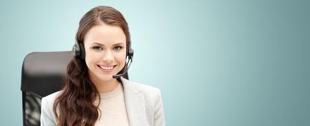 Concepto de personas, servicio en línea, comunicación y tecnología - operador de línea de ayuda femenina sonriente con auriculares sobre fondo azul