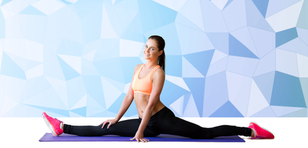 splits: fitness, sport, exercising, stretching and people concept - smiling woman doing splits on mat over blue low poly background