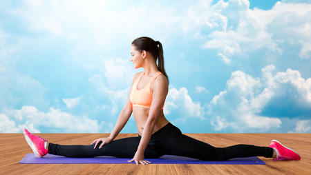 splits: fitness, sport, exercising, stretching and people concept - smiling woman doing splits on mat over wooden floor and sky with white clouds background