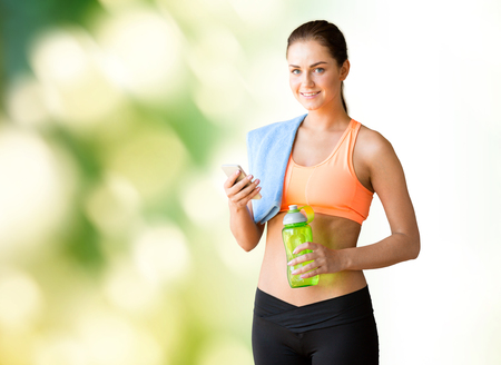 water concept: fitness, sport, technology and people concept - happy woman with smartphone, towel and bottle of water over green natural background Stock Photo