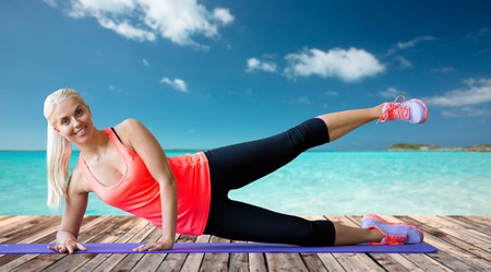 berth: fitness, sport, exercising and people concept - smiling woman raising leg on mat over sea and wooden berth at resort background Stock Photo