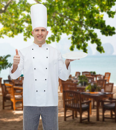 empty of people: cooking, profession, advertisement and people concept - happy male chef cook holding something on empty plate and showing thumbs up over restaurant lounge on beach