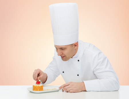 eating pastry: cooking, profession, haute cuisine, food and people concept - happy male chef cook decorating dessert over beige background Stock Photo