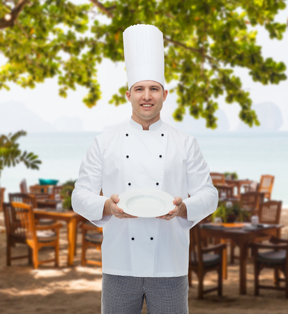 empty of people: cooking, profession, advertisement and people concept - happy male chef cook showing something on empty plate over restaurant lounge on beach