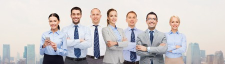 business, people, corporate, teamwork and office concept - group of happy businesspeople with crossed arms over city background Banque d'images