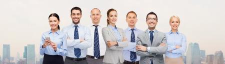 Unternehmen, Menschen, Unternehmen, Teamarbeit und Bürokonzept - Gruppe von glücklichen Geschäftsleute mit verschränkten Armen über Stadt Hintergrund
