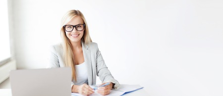 computer table: business and education concept - indoor picture of smiling woman with documents and pen Stock Photo