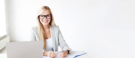 negocios y la educación concepto - imagen interior de mujer sonriente con los documentos y la pluma