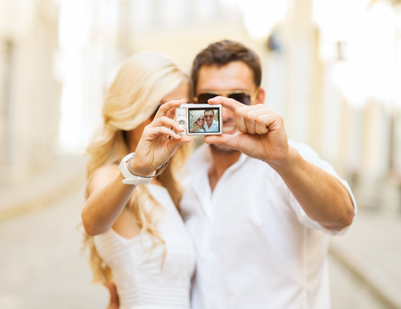 couple dating: summer holidays, travel, vacation, tourism and dating concept - travelling couple taking photo picture with camera