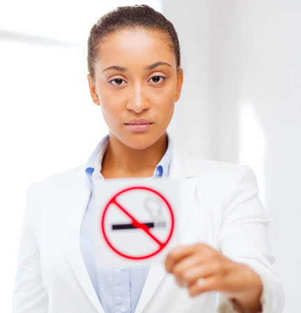 crossed cigarette: health and healthcare concept - picture of african woman with restriction no smoking sign Stock Photo