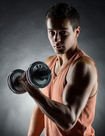 pesas: deporte, culturismo, el entrenamiento y la gente concepto - hombre joven con mancuernas flexionando los músculos sobre fondo gris