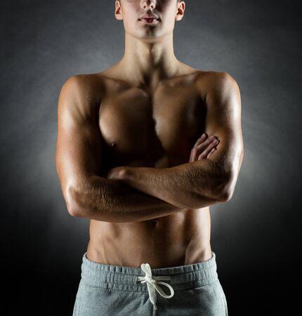 sportsman: deporte, el culturismo, la fuerza y ??la gente concepto - joven de pie sobre fondo negro Foto de archivo