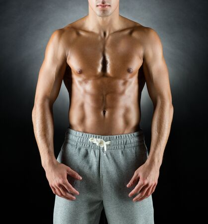 fit: sport, bodybuilding, strength and people concept - young man standing over black background