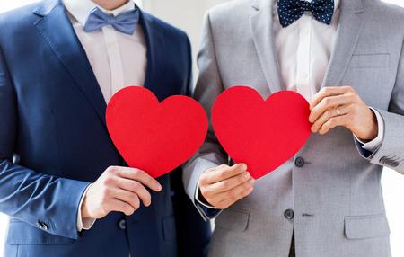 les gens, l'homosexualité, le mariage de même sexe, Saint Valentin et l'amour notion - close up of heureux marié mâle couple gay tenant rouges en forme de coeur de papier sur mariage