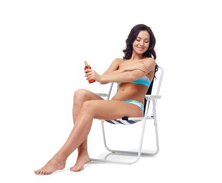 pulverizador: gente, moda, traje de baño, verano y concepto de la playa - mujer joven feliz en bikini tomando el sol traje de baño en silla plegable y aplicar protector solar a la piel
