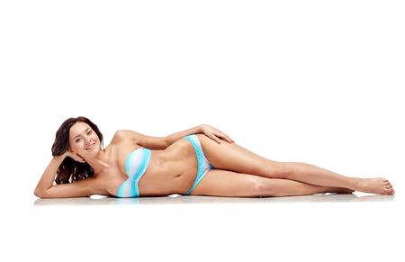 people, fashion, swimwear, summer and beach concept - happy young woman lying in bikini swimsuit