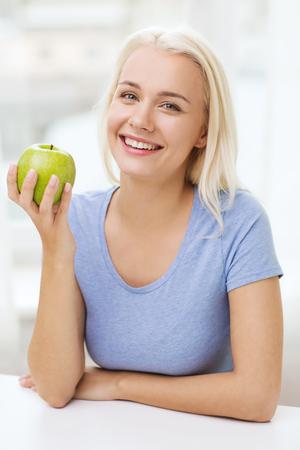 alimentos saludables: alimentación saludable, alimentos orgánicos, frutas, la dieta y el concepto de la gente - la mujer feliz come la manzana verde en el país Foto de archivo