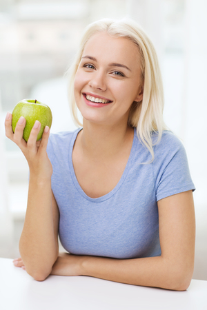 food healthy: healthy eating, organic food, fruits, diet and people concept - happy woman eating green apple at home