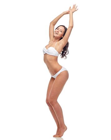 mooie vrouwen: mensen, mode, badmode, de zomer en het strand concept - gelukkige jonge vrouw poseren in witte bikini zwembroek dansen met opgeheven handen
