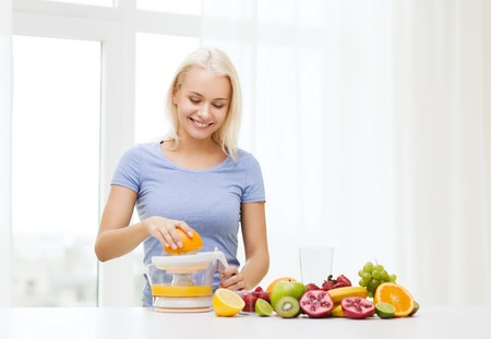 juice squeezer: healthy eating, vegetarian food, diet, detox and people concept - smiling woman with squeezer squeezing fruit juice at home