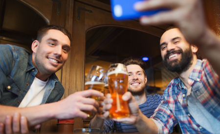 bachelor: people, leisure, friendship, technology and bachelor party concept - happy male friends with smartphone taking selfie and drinking beer at bar or pub Stock Photo
