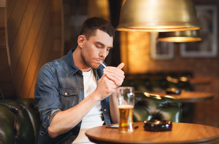 alcoholic man: people and bad habits concept - man drinking beer and smoking cigarette at bar or pub